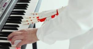L'ingegnere dello scienziato sta giocando il piano con la mano robot della protesi Gioco due mani, una mano prostetica robot e de video d archivio