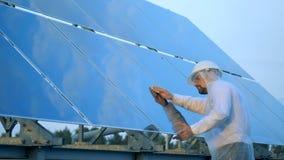 L'ingegnere di manutenzione sta pulendo la superficie glasslike di una batteria solare Concetto ecologico di energia archivi video