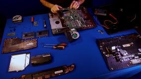 L'ingegnere Disassembles il computer portatile per la riparazione Scheda madre del computer portatile Rivestimenti di tempo archivi video