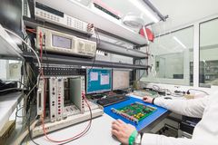 L'ingegnere effettua una prova dei moduli elettronici finiti Laboratorio per le prove e l'adeguamento di elettronico Immagine Stock