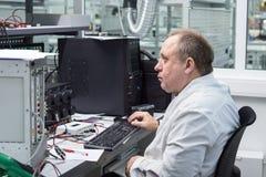 L'ingegnere effettua una prova dei moduli elettronici finiti Laboratorio per le prove e l'adeguamento di elettronico Fotografia Stock