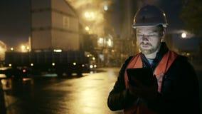 L'ingegnere in elmetto protettivo con un computer della compressa esamina il camion sulla fabbrica dell'industria pesante video d archivio