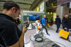 L'ingegnere fa funzionare il robot industriale di KUKA in cabina della società di Huawei Fotografie Stock Libere da Diritti