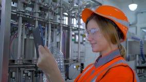 L'ingegnere femminile sul lavoro, giovane donna del tecnico della fabbrica nel casco usa la compressa del computer e la fabbricaz archivi video