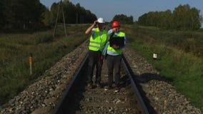 L'ingegnere ferroviario controlla le rotaie ferroviarie con l'assistente archivi video