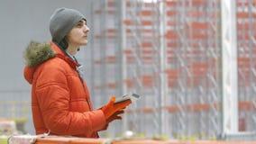 L'ingegnere guarda la compressa e dai lati dentro un nuovo magazzino moderno stock footage