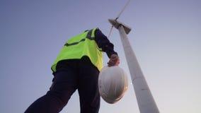 L'ingegnere Hold in sue mani un casco bianco e passi avanti al mulino a vento davanti lui archivi video