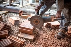 L'ingegnere industriale che lavora ai mattoni di taglio al cantiere, facendo uso di una smerigliatrice, mitra elettrico ha visto  fotografie stock