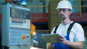 L'ingegnere industriale sta facendo funzionare un computer portatile accanto ad una console di controllo video d archivio
