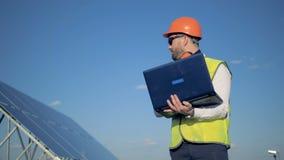 L'ingegnere maschio è batteria solare vicina diritta e scrivere sul suo computer portatile Concetto di energia alternativa stock footage