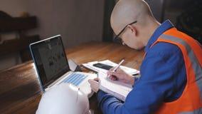 L'ingegnere maschio che lavora nella stanza per un computer portatile in camici, casco si trova accanto lui sulla tavola video d archivio