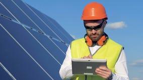 L'ingegnere maschio sta esaminando un pannello solare e sta notando qualcosa in suo computer archivi video