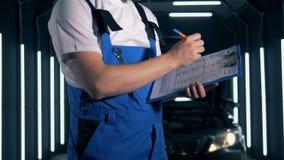 L'ingegnere maschio sta scrivendo un rapporto dopo l'ispezione dell'automobile Concetto di servizio dell'automobile archivi video