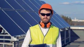 L'ingegnere maschio sta stando contro lo sfondo dell'gli elementi solari Ritratto archivi video