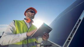 L'ingegnere maschio sta stando su un tetto vicino ad una batteria solare con un computer della compressa archivi video