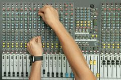 L'ingegnere sano maschio passa lavorare all'audio console di miscelazione immagine stock