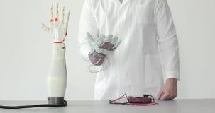 L'ingegnere sta collaudando la mano robot della protesi che ripete il movimento della sua mano in guanto con i sensori video d archivio