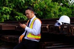 L'ingegnere sta lavorando con lo Smart Phone con il grande BAC dell'industria fotografie stock