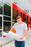 L'ingegnere sul cantiere in un casco arancio ed in una maglietta bianca tiene il piano di uno stroitelsv a disposizione Controllo fotografia stock