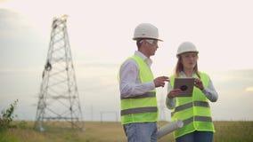 L'ingegneria che lavora alla torre ad alta tensione, controlla le informazioni sugli impiegati uomo e donna del computer due dell stock footage