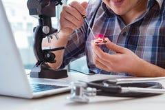 L'ingegneria di alta precisione con l'uomo che lavora con il microscopio Fotografie Stock