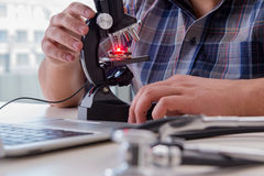 L'ingegneria di alta precisione con l'uomo che lavora con il microscopio Fotografia Stock