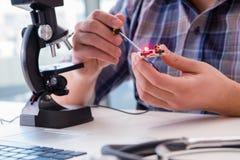 L'ingegneria di alta precisione con l'uomo che lavora con il microscopio Fotografia Stock Libera da Diritti
