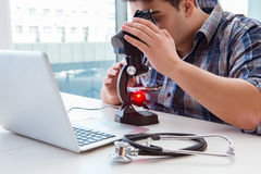 L'ingegneria di alta precisione con l'uomo che lavora con il microscopio Immagine Stock