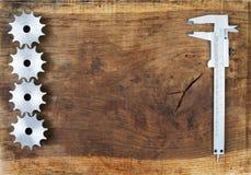 L'ingegneria foggia gli ingranaggi ed il calibro sulla tavola di legno Sfera differente 3d Fotografie Stock