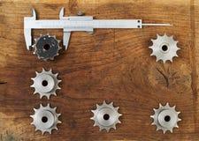 L'ingegneria foggia gli ingranaggi ed il calibro sulla tavola di legno Sfera differente 3d Immagine Stock
