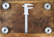 L'ingegneria foggia gli ingranaggi ed il calibro sulla tavola di legno Sfera differente 3d Immagini Stock