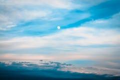 L'inizio del tramonto mentre la luna è alta nel cielo Immagini Stock Libere da Diritti