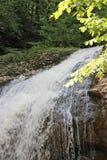 L'inizio di piccola cascata della foresta nelle montagne fotografia stock