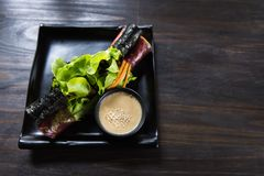 L'insalata arriva a fiumi il piatto nero immagine stock