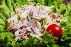 L'insalata con il prosciutto ed i funghi su una lattuga coprono di foglie immagini stock libere da diritti