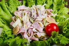 L'insalata con il prosciutto ed i funghi su una lattuga coprono di foglie fotografia stock libera da diritti