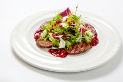 L'insalata con il vitello arrostito e l'insalata fresca va su un piatto bianco Fotografia Stock Libera da Diritti