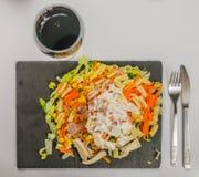 L'insalata con la salsa del pollo, del bacon e di pasta registra con vino rosso dentro Immagini Stock