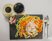 L'insalata con la salsa del pollo, del bacon e di pasta registra con vino rosso dentro fotografie stock