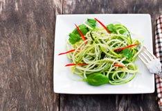 L'insalata degli spaghetti dello zucchini con basilico e il paprica sull'quadrato su plat Fotografia Stock