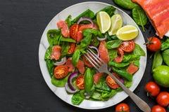 L'insalata di color salmone fresca con spinaci, i pomodori ciliegia, la cipolla ed il basilico in piatto di marmo con porgono il  fotografie stock libere da diritti