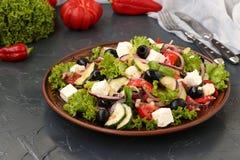L'insalata greca è situata su un piatto su un fondo scuro fotografia stock