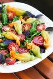 L'insalata stagionale con la rucola, i pomodori ciliegia, il basilico e lo zucchini fiorisce Fotografia Stock