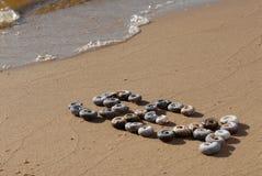"""L'inscription """"mer """"est écrite par le petit shellson de mer l'à sable jaune image stock"""
