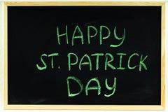 L'inscription avec la craie verte sur un tableau : Le jour de St Patrick heureux Photographie stock