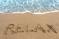 L'inscription détendent sur le sable Image libre de droits