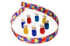 L'inscription d'autisme avec des chiffres et le puzzle modèlent le ruban sur le fond blanc Photo stock
