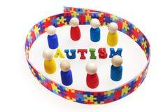 L'inscription d'autisme avec des chiffres et le puzzle modèlent le ruban sur le fond blanc Photos libres de droits
