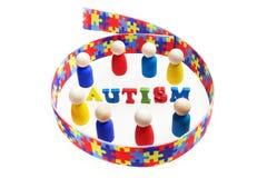 L'inscription d'autisme avec des chiffres et le puzzle modèlent le ruban sur le fond blanc Image stock