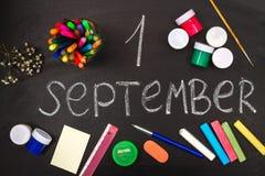 L'inscription est le 1er septembre Entouré par la craie et les fournitures scolaires sur un conseil noir Images stock